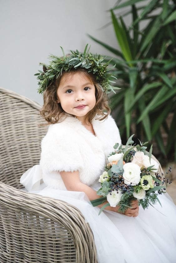a white dress with a full tutu skirt, a white faux fur coverup and a textural greenery crown for a winter flower girl