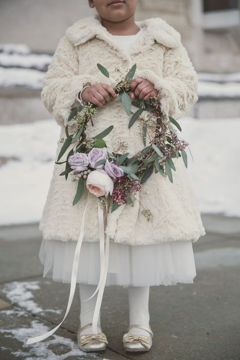 a white dress with a tutu skirt, white tights, gold shoes, a neutral faux fur coat and a flower wreath