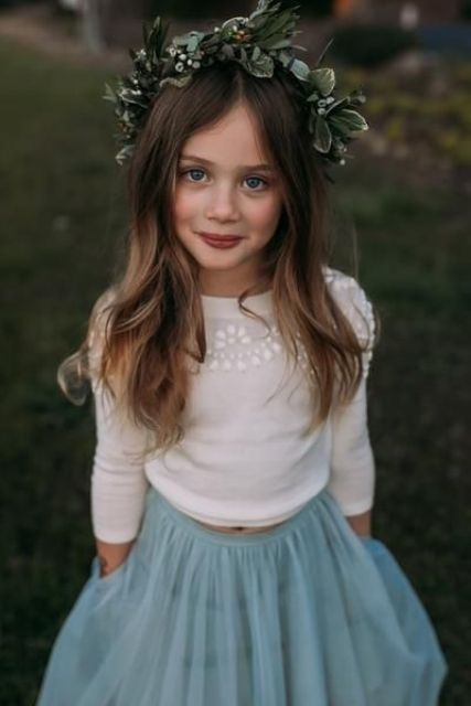 a white embellished top, a blue tulle A-line skirt, a greenery and berry crown for a winter flower girl
