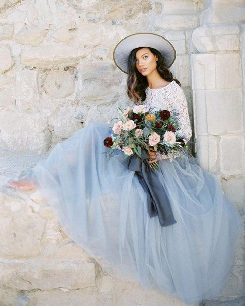 a white lace top with long sleeves, a serenity blue tulel midi skirt and a hat