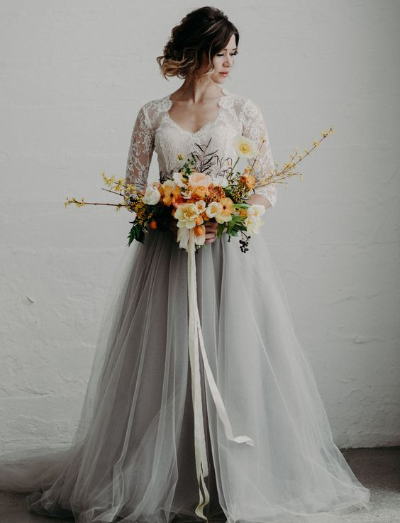 a white lace top with long sleeves and a grey tulle maxi skirt with a train for a modern and romantic bridal look