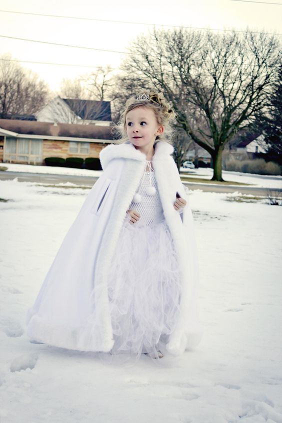 a white maxi dress with a tutu skirt, a white faux fur cloack and a crown for a winter flower girl look