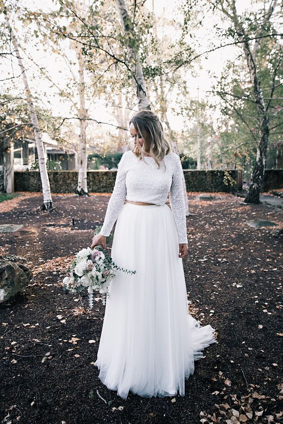 a white sparkling crop top with long sleeves, a white tulle maxi skirt with a train for a modern bridal outfit