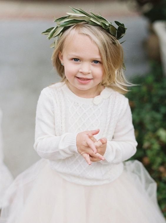a white sweater, a white tutu skirt and a greenery crown for a stylish casual winter flower girl outfit