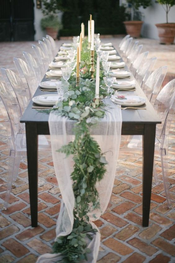 a white tulle and greenery table runner with candles in elegant metallic candle holders for a fresh look