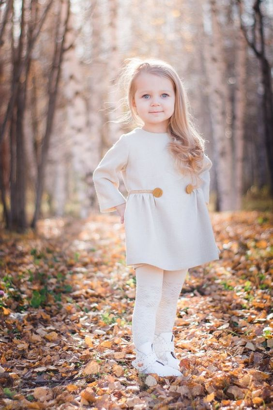 a white warm mini dress with long sleeves and buttons, white tights and geometric shoes for a modern winter flower girl