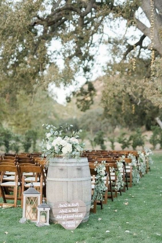 a whitewashed barrel with greenery and white blooms plus candle lanterns and a heart-shaped sign for a rustic wedding