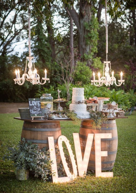 a wine barrel dessert and drink station with crystal chandeliers, greenery, signs and lots of desserts and drinks for a rustic wedding