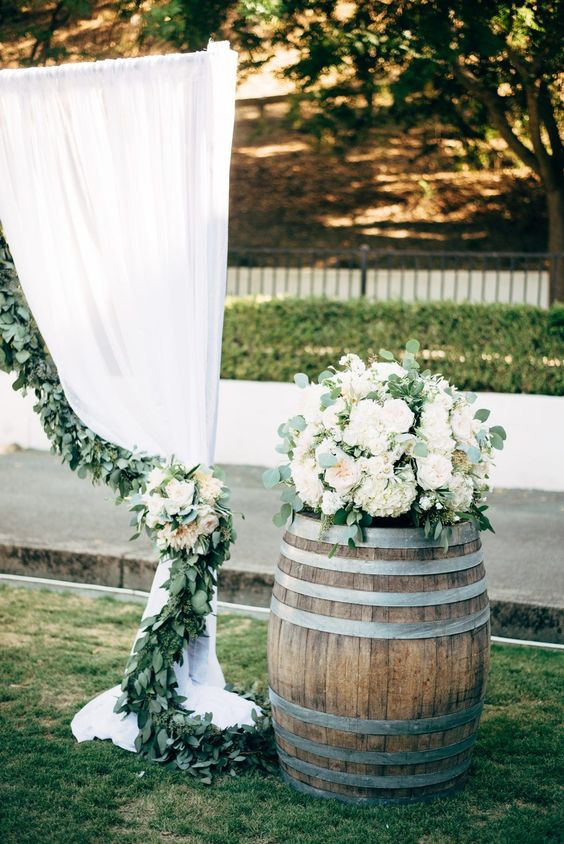 a wine barrel with a white floral arrangement and greenery is a lovely idea for rustic wedding decor and is easy to realize