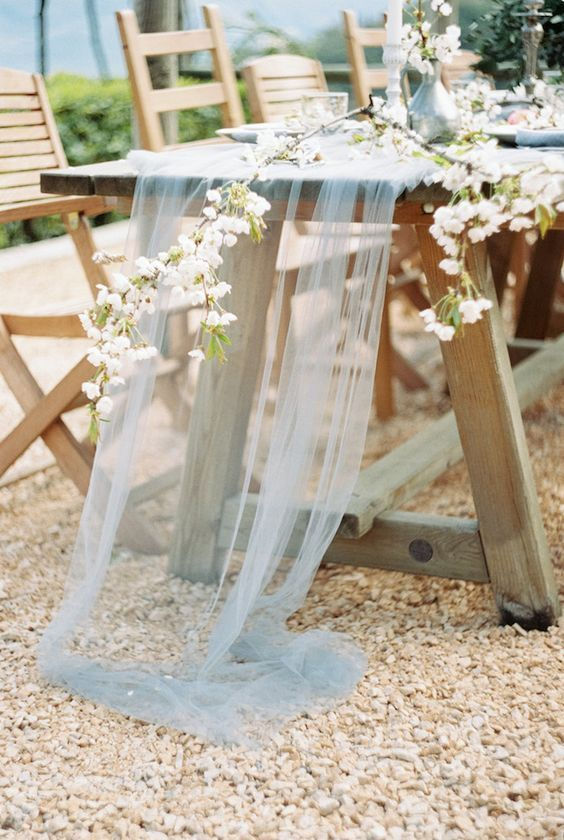 an airy powder blue tulle table runner and cascading blooming branches make the tablescape very natural and tender