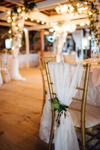 an elegant wedding chair cover idea - gold chairs draped in white tulle and greenery
