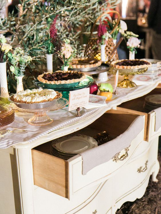 an elegant wedding pie bar of a vintage sideboard, with plates and cutlery in drawers, some blooms and greenery, fruits and delicious pies