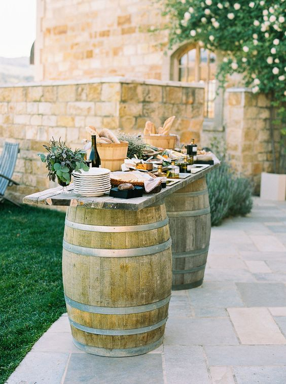 an olive oil tasting bar with bread, oil, olives and other stuff, made of two barrels and some wooden planks