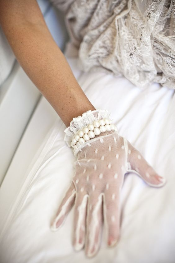 delicate white lace gloves with polka dots, ruffles and two rows of pearls for a refined feel
