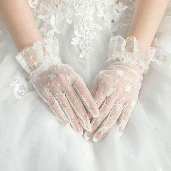 elegant white mesh gloves with ffloral appliques and wide ruffles on the wrists look chic