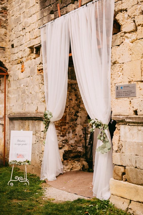 elegant white tulle curtains with fresh eucalyptus can decorate the entry to a reception or ceremony space