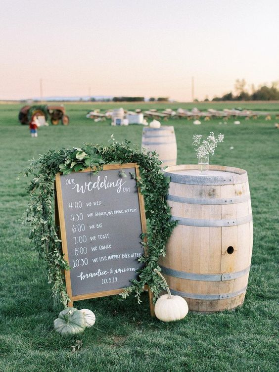 rustic wedding decor with a wine barrel, a chalkboard sign with greenery and some simple pumpkins for a fall wedding