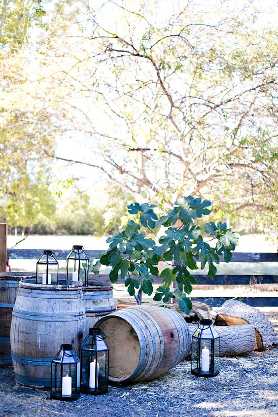 rustic wedding decor with barrels, candle lanterns and some greenery is very chic and very cozy
