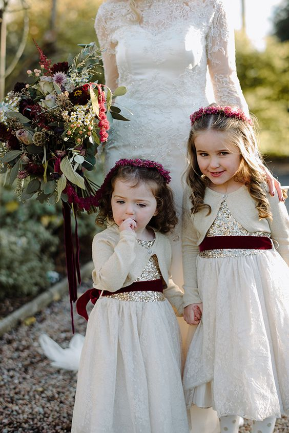 whimsy dresses with gold sequin bodices, white lace skirts, neutral cardigans and burgundy velvet sashes