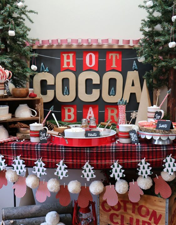 a Christmas hot cocoa bar with paper and pompom garlands, mugs, sweets and candies and a plaid tablecloth