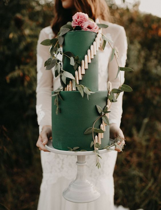 a boho green wedding cake with gold candle detailing and fresh greenery and light pink blooms for a boho summer wedding