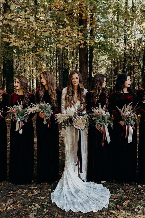 a boho lace A-line wedding dress with bell sleeves and a train, burgundy velvet maxi dresses with high necklines for bridesmaids