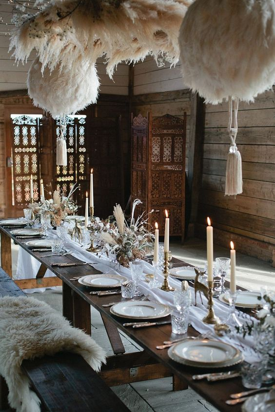 a boho lux wedding tablescape with a white runner, gold figurines, candles, dried blooms and grasses and feather balls over the table