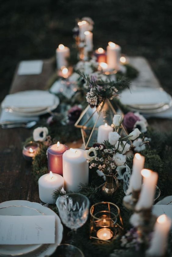 a boho lux winter wedding table setting with candles in white and purple, matching blooms, a fir runner and elegant plates with a gold rim