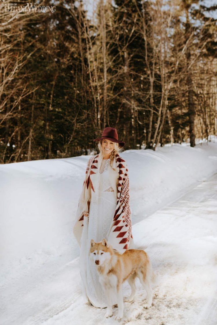 a boho winter bride wearing a boho lace sheath wedding dress, a burgundy hat and a printed coverup in burgundy and white