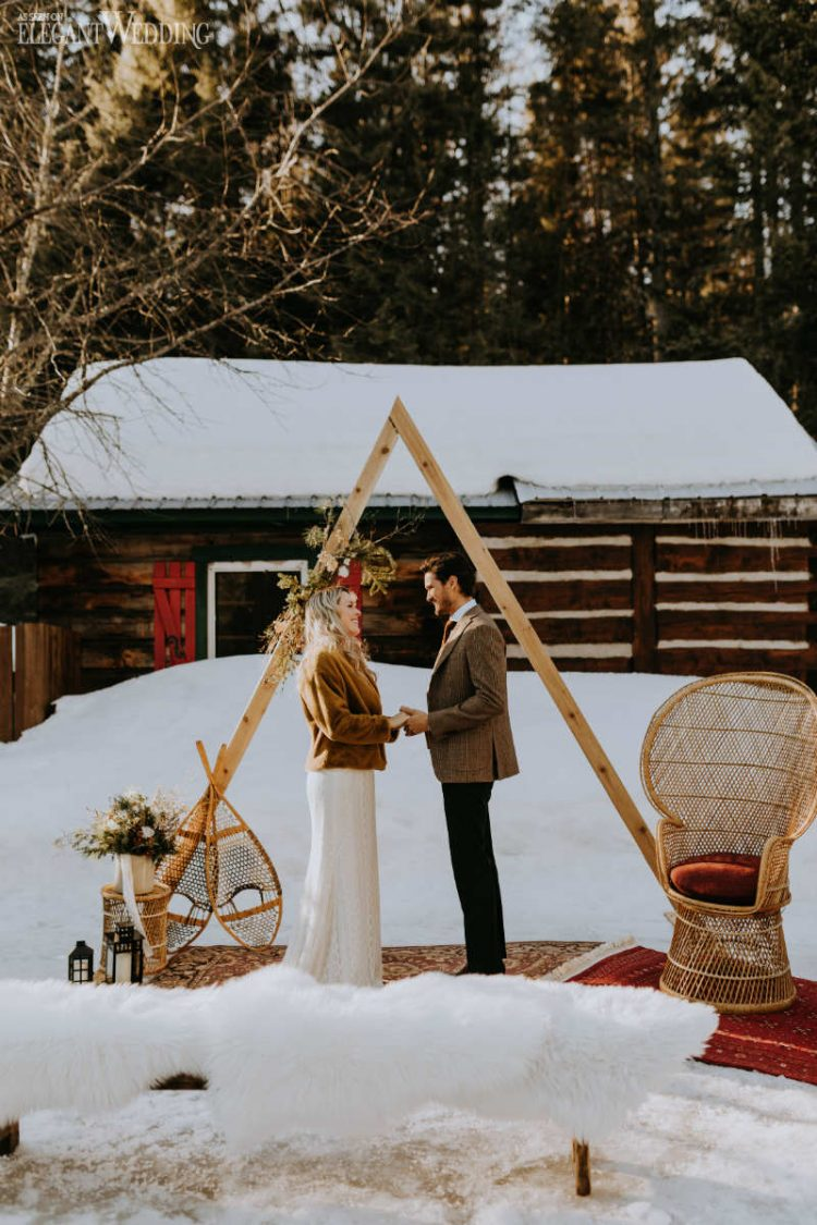 a boho winter wedding space with boho rugs, faux fur, an arch decorated with dried blooms and leaves, candle lanterns