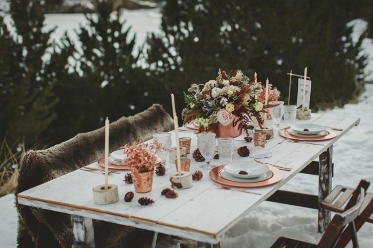 a boho winter wedding tablescape with candles, copper chargers and candleholders, neutral wintry blooms and pale greenery