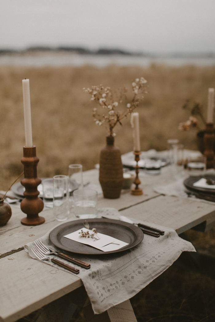 a boho winter wedding tablescape with pritned napkins, porcelain plates and vases, wooden candleholders
