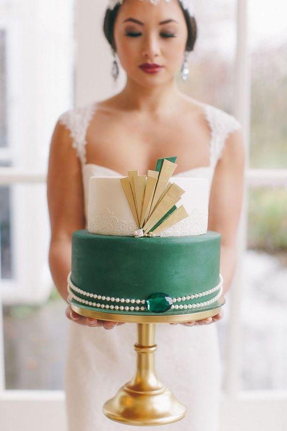 a bold art deco wedding cake with a white lace and sleek green tier, gold detailing and a pearl necklace with an emerald