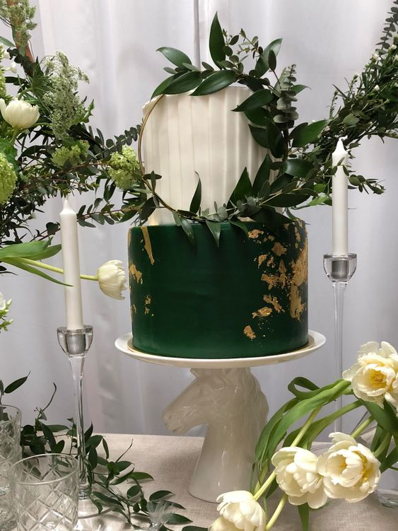 a bold emerald and white wedding cake with a pleated tier and a sleek one with gold leaf and a hoop with greenery for a modern wedding