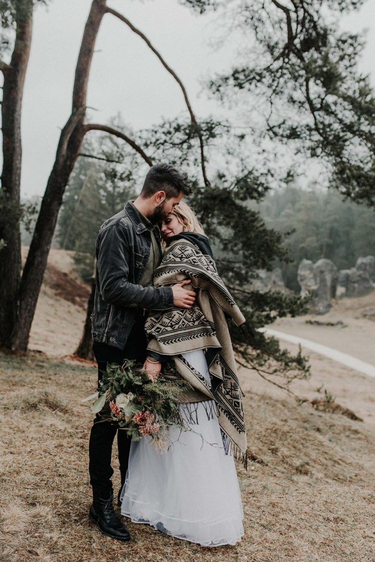 a bride covered up with a boho fringed printed piece and a groom wearing a black leather jacket and boots