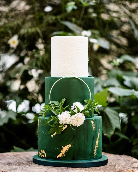 a bright and chic wedding cake in white and emerald, with a marble tier and gold touches, a hoop with greenery and blooms