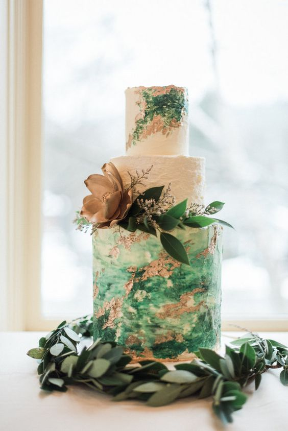 a bright white, green and copper wedding cake with watercolor tiers, leaves and a gilded flower is a romantic idea