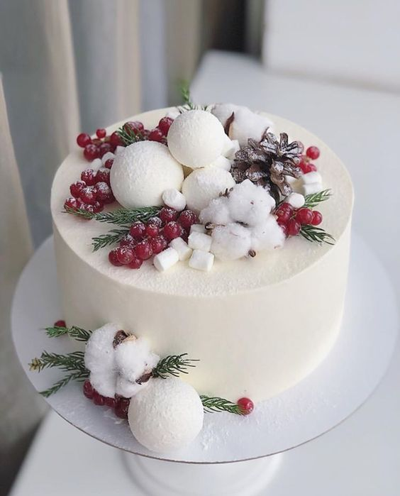 a buttercream wedding cake topped with berries, greenery, snowballs and pinecones plus masrhmallows