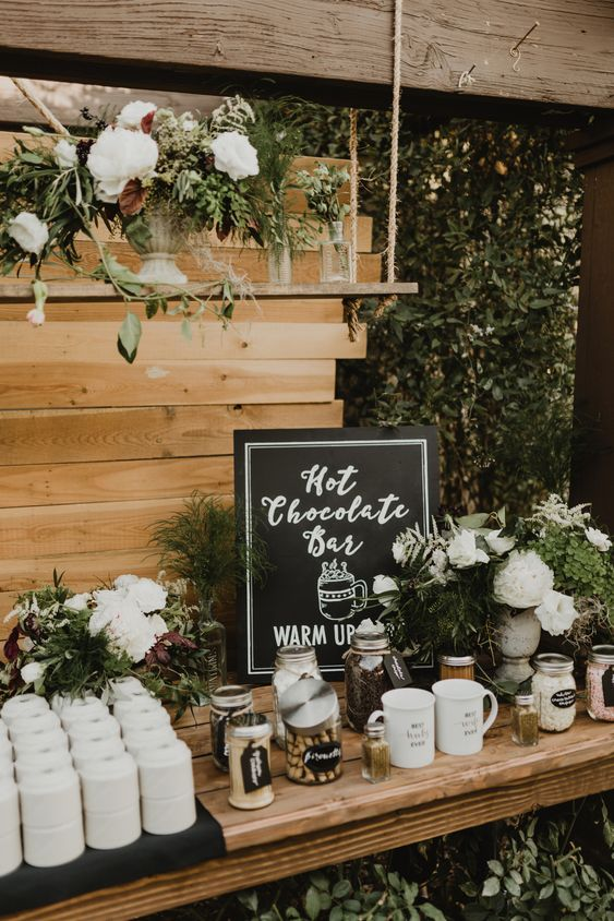 a chic and natural hot chocolate bar with a sign, jars with candies and toppings, mugs, greenery and neutral blooms