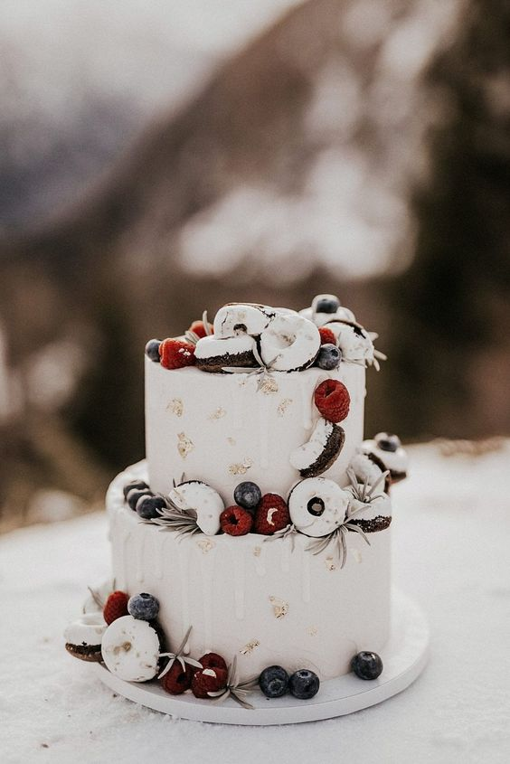 a chic white frosted wedding cake with gold leaf, white drip, berries and glazed donuts is amazing