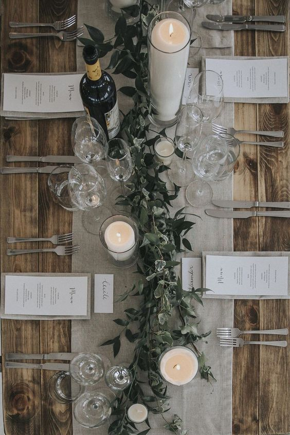 a chic winter wedding tablescape with a grey table runner and linens, candles, a greenery runner and elegant cutlery
