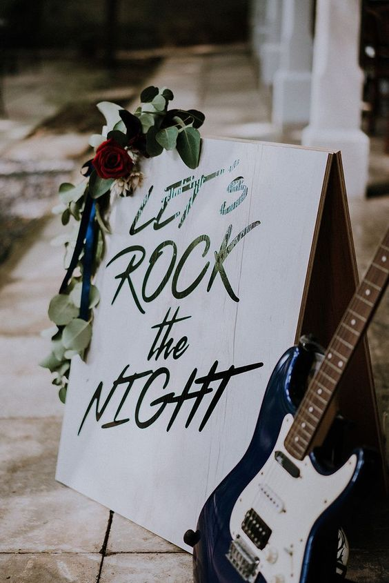 a cool wedding decoration of a sign, greenery and red blooms and a guitar is an easy idea to realize yourself and it looks cool