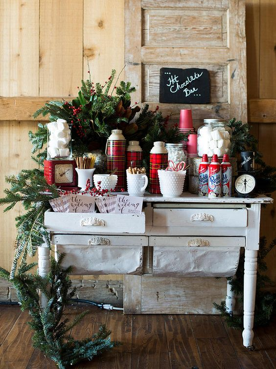 a cozy Christmas hot chocolate bar with evergreens, plaid elements, a chalkboard sign, a Christmas arrangement