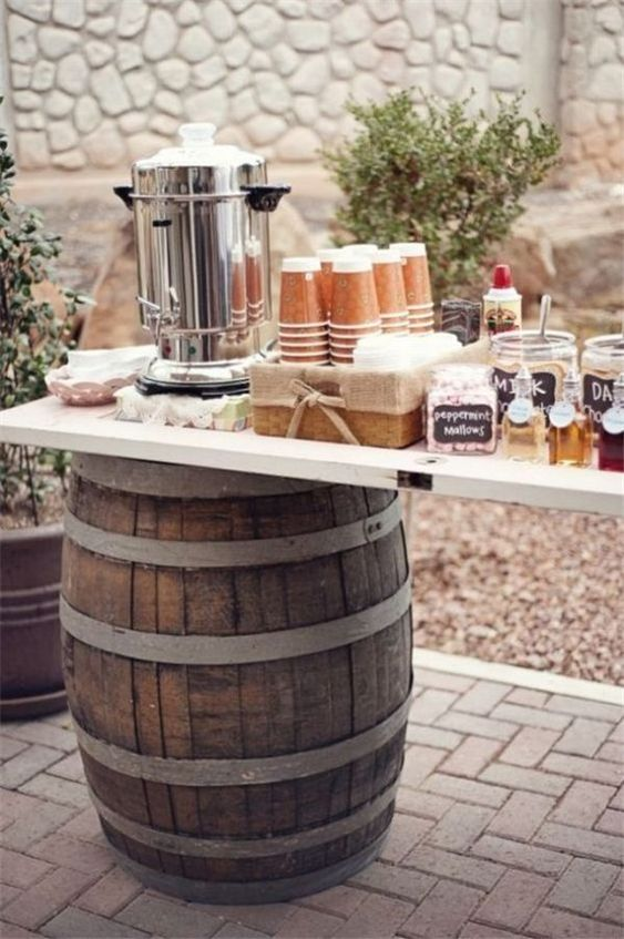 a cozy hot chocolate bar placed on barrels, with evergreens around, some syrups and some caramel
