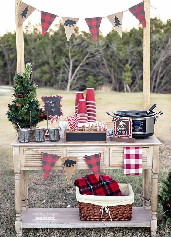 a cozy rustic hot chocolate bar with plaid banners, metal buckets, a mini Christmas tree and some cups