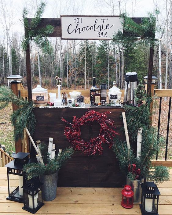 a cozy winter hot chocolate bar done with evergreens, branches, candle lanterns and some cups, chocolate and liquors