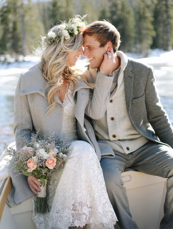 a dove grey coat for the bride, a grey jacket and pants for the groom and touches of cream