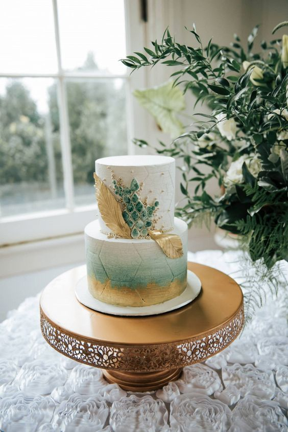 a fantastic wedding cake with a white and an ombre green tier, gold brushstrokes and leaves and green marble like pieces