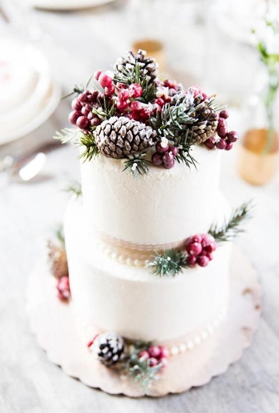 a frosted wedding cake with berries, fir, pinecones and ribbons is a stylish wedding dessert to rock