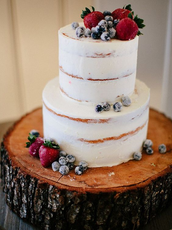 a frosty wedding cake topped with sugared and fresh berries is ideal for a rustic winter wedding